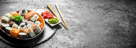 Traditional Japanese rolls and sushi in a plate on a stone Board. On black rustic background stock photo