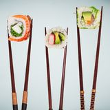 Traditional japanese sushi pieces placed between chopsticks on pastel color background. Royalty Free Stock Image