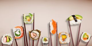 Traditional japanese sushi pieces placed between chopsticks on pastel color background. Stock Image