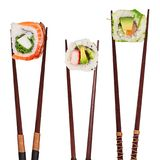 Traditional japanese sushi pieces placed between chopsticks, separated on white background. Royalty Free Stock Photos