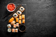 Traditional Japanese sushi rolls with ginger and soy sauce on a black stone Board royalty free stock photography