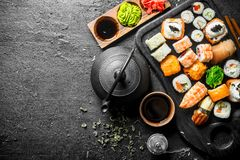 Traditional Japanese sushi and rolls with green tea in the teapot royalty free stock photos
