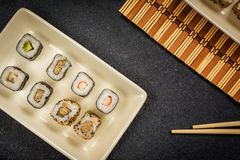 Sushi rolls hosomaki and uramaki. Traditional japanese sushi rolls hosomaki  and chopsticks  on stone desk Royalty Free Stock Photo