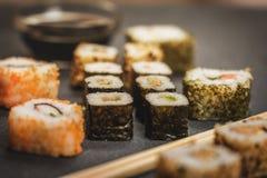 Sushi rolls hosomaki and uramaki. Traditional japanese sushi rolls hosomaki,uramaki  and chopsticks and soy sauce on stone desk Royalty Free Stock Images