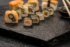 Sushi rolls hosomaki and uramaki. Traditional japanese sushi rolls hosomaki and uramaki and chopsticks on stone desk Stock Photos