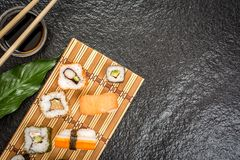 Sushi rolls hosomaki and uramaki. Traditional japanese sushi rolls hosomaki,uramaki, nigiri  and chopsticks and soy sauce on stone desk top view Stock Photo