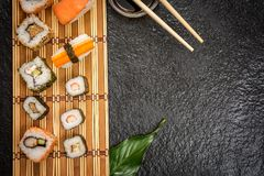Sushi rolls hosomaki and uramaki. Traditional japanese sushi rolls hosomaki,uramaki, nigiri  and chopsticks and soy sauce on stone desk top view Royalty Free Stock Photo
