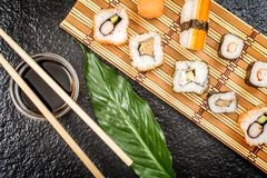 Sushi rolls hosomaki and uramaki. Traditional japanese sushi rolls hosomaki,uramaki, nigiri  and chopsticks and soy sauce on stone desk top view Royalty Free Stock Image