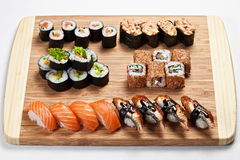 Traditional japanese sushi rolls and nigiri  on a wooden board. Sushi rolls served on a wooden board background. Spicy Gunkans and sushi nigiri with salmon and Royalty Free Stock Photos