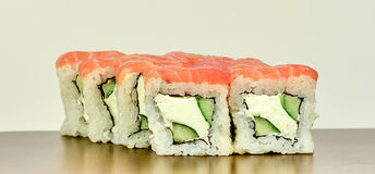 Traditional japanese sushi rolls philadelphia with salmon. And cucumber and cream cheese on white and brown background Royalty Free Stock Photos