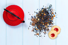 Traditional Japanese teapot, tea leaves and cookies. Traditional Japanese red teapot, tea leaves and cookes on wooden table Stock Photography