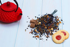 Traditional Japanese teapot, tea leaves and cookies. Traditional Japanese red teapot, tea leaves and cookes on wooden table Royalty Free Stock Photography