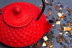 Traditional Japanese teapot and tea leaves. Traditional Japanese red teapot and tea leaves on black slate Stock Photo