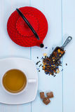 Traditional Japanese teapot, tea, leaves and sugar. On wooden table Royalty Free Stock Images