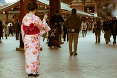 Traditional Japanese woman dressed in Kimono posing at the entrance of Senso-ji temple, Asakusa, Tokyo, Japan. Senso-ji in Asakusa is one of the most popular and Royalty Free Stock Photography