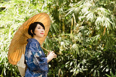 Traditional Japanese woman in the park Stock Photography