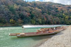 Traditional japanese wooden boat anchored on green river in autu Royalty Free Stock Photo