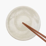 Traditional Japanese wooden chopstick on white ceramic plate royalty free stock photography
