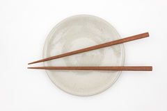 Traditional Japanese wooden chopstick on white ceramic plate royalty free stock images