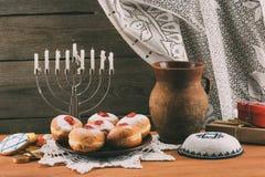 Traditional jewish menorah, Kippah and donuts. Traditional jewish menorah, Kippah, ceramic jug, gifts and donuts for hanukkah celebration Royalty Free Stock Images