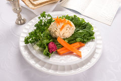 Traditional Jewish passover  Gefilte Fish. Traditional Jewish passover food gefilte fish with carrots, parsley, horseradish, and lettuce on white linen table Royalty Free Stock Image