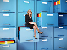 Traditional job. Businesswoman sit on drawer of  cabinet folder Royalty Free Stock Photo