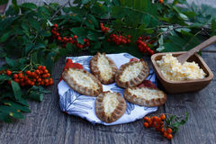 Traditional Karelian pasties on rustic wooden background. Finish traditional food, warm,crust,rice incide,with egg button,rowan-berry towel,green leaf Royalty Free Stock Photos