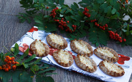 Traditional Karelian pasties on rustic wooden background. Finish traditional food, warm,crust,rice incide,with egg button,rowan-berry towel,green leaf Stock Photography