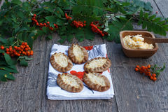 Traditional Karelian pasties on rustic wooden background. Finish traditional food, warm,crust,rice incide,with egg button,rowan-berry towel,green leaf Royalty Free Stock Photography