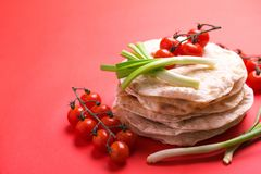Indian flatbread chapati, green onion, cherry tomato. Color surge trend. Traditional Kerala Indian cuisine. Homemade flatbread chapati with green onion and stock images