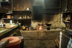 Traditional kitchen in old Nepali house in small remote village. In Himalayas with open fire place, smoking coal, kettles, frying pans and pots. Interior of a royalty free stock image