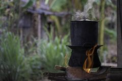 Traditional Kitchen, Sticky Rice Steaming Pot - The local kitchen in the village.Black pot boiling for the rice cooker on the fire. D stove next to firewood pile royalty free stock image