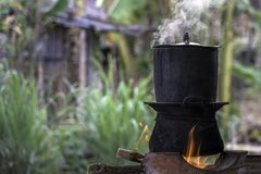 Traditional Kitchen, Sticky Rice Steaming Pot - The local kitchen in the village.Black pot boiling for the rice cooker on the fire. D stove next to firewood pile stock photos