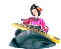 Traditional Korean Doll and Musical Insturment. Beautiful Korean doll wearing traditional costume and playing a traditional instrument.  Isolated on white Royalty Free Stock Photo