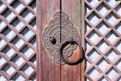 Traditional Korean wooden doors with metal ring. Traditional Korean door handle/latch with metal ring and lattice design Royalty Free Stock Photos
