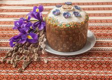 Kulich, willow twigs and iris. Traditional Kulich with chocolate icing, willow twigs and iris. Palm Sunday. On the package of the Easter cake the first letters Royalty Free Stock Photos