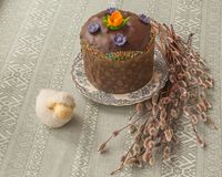 Kulich, willow twigs and lamb. Traditional Kulich with chocolate icing, willow twigs and lamb. Palm Sunday. On the package of the Easter cake the first letters Royalty Free Stock Photos