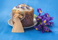 Kulich, iris and straw angel. Traditional Kulich with  icing, iris  and  straw angel.  On the package of the Easter cake the first letters of the Easter cry ` Royalty Free Stock Image