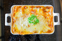 Traditional lasagna made with minced beef bolognese sauce topped. With basil leafs royalty free stock photo
