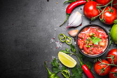 Traditional Latin American mexican salsa sauce. And ingredients on black stone table. Top view copy space stock photos