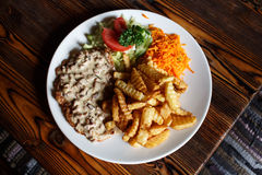Traditional Latvian rustic dish: pork chop with cream sauce, car. Rot and cabbage salad, potatoes fries royalty free stock photos