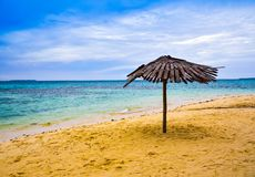 Traditional lazy hut yellow sandy beach in the clear blue morning sky royalty free stock image