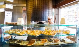 Traditional Lebanese sweets and pizza. BEIRUT, LEBANON - NOVEMBER 1, 2017 - Man selling traditional Lebanese sweets and pizza stock images