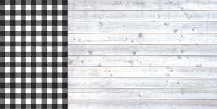 Traditional light grey plank with black white tablecloth. Traditional light grey wooden plank with copy space and tablecloth checkered white and black Stock Image