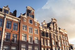 Traditional living houses of old Amsterdam. Netherlands. Facades over cloudy sky Royalty Free Stock Image