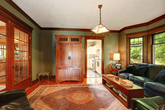 Traditional living room interior with leather sofa set. Traditional living room interior with black leather sofa set, hardwood floor, rug and antique cabinet Stock Photo