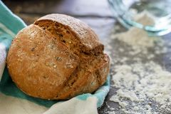 Traditional loaf on a dish towel. A piece of a handmade bread with sesame seeds on a white and blue dish towel and flour scattered all over the ground coming out stock images
