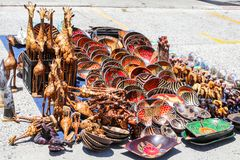 Traditional local african souvenir market on the street with rows of carved hand painted wooden bowls, giraffes, elephants with co stock image