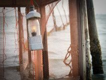 Traditional local fishing lamp is hanging on pole behind orange net with lake background. Hope and target concept Stock Image