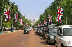 Traditional London taxis, black cabs. LONDON - July 15 : traditional London taxi, black cab on the street decorated with british flags and leading to the Mall Royalty Free Stock Photography